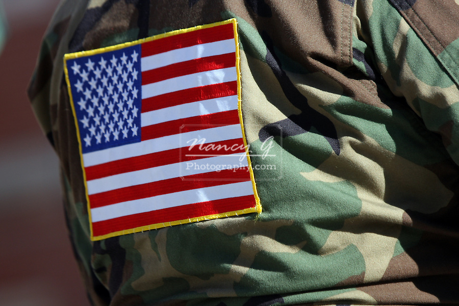 An American Flag patch sewn to the back of a camouflage jacket