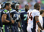 Seattle Seahawks quarterback Russell Wilson and fullback Michael Robinson tease Denver Broncos cornerback Champ Bailey at CenturyLink Field in Seattle, Washington on  August 17, 2013. The Seattle Seahawks beat the Broncos 40-10.     ©2013. Jim Bryant Photo. All Rights Reserved.