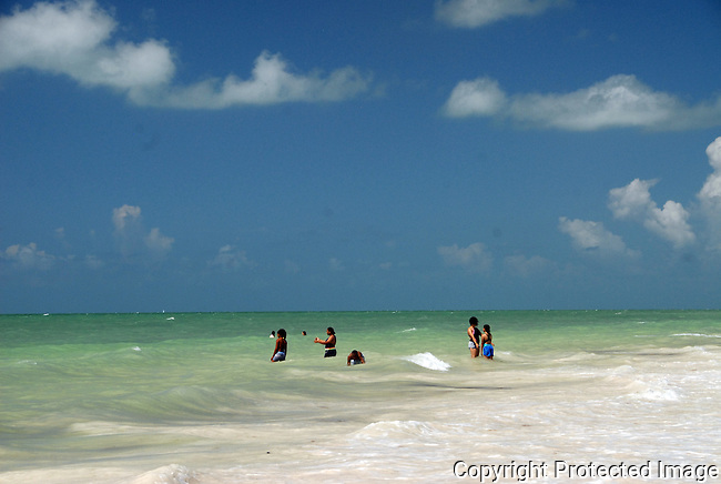 people wading in the soft grren surf of Silver Spur Beach, Bahia Honda State Pk, Florida Keys