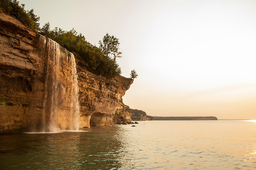 Spray Falls waterfall falls from a sandstone cliff in the backcountry of Pictured Rocks National Lakeshore near Munising, Michigan.