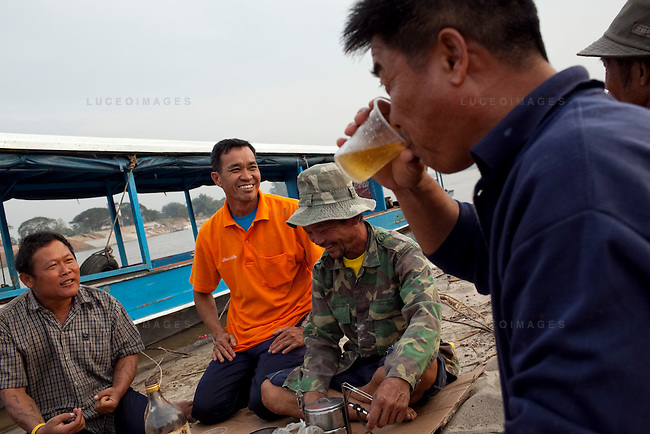 "Thai tour boat operators from left, Mon, Peng, Noi, and Bounsri drink Lao beer and whiskey on a beach in Myanmar on the Mekong River near Sop Ruak, Thailand. ""Some times business is not good because the water is low from the dams in China that we have to take boats out,"" Noi said. Photo taken on Thursday, December 10, 2009. Kevin German / Luceo Images"