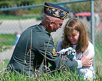 NEWS&GUIDE PHOTO / PRICE CHAMBERS.American Legion Post 43 Commander David Bentlage comforts Jackie Williams on Memorial Day at Aspen Hill Cemetery. Williams sits where she plans to bury her veteran father on Tuesday, May 26 next to her grandfather, a veteran of World War I. Her veteran father Jack Richards also served as commander for the American Legion.