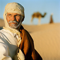 A camel trader looks into the distance in the Sahara desert in the south of Tunisia
