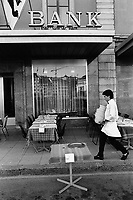 Switzerland. Geneva. A waiter sets the restaurant's tables on an open-air terrace. Bank window in the financial district. © 1990 Didier Ruef