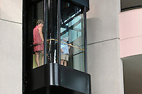 Mother & child in a glass enclosed elevator.
