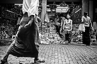 A man in a tradional Burmese longyi passes by a shop with a large stock of sandals on offer, in the Scott market in Yangon.