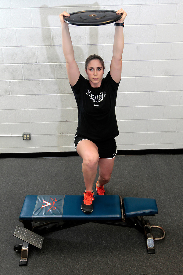 Assistant UVa strength and conditioning coach   Jenny Shultis demonstrates the overhead step ups exercise at the McCue Center weight room on campus at the University of Virginia in Charlottesville, VA. Photo/Andrew Shurtleff