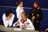 (L-R) Anna Bessonova of Ukraine, Marina Shpekt with Olga Kapranova of Russia and Natalya Godunko or Ukraine  smile while Olga completes press information form before 2006 Deriugina Cup Grand Prix event at Kiev, Ukraine on March 16.. (Photo by Tom Theobald)