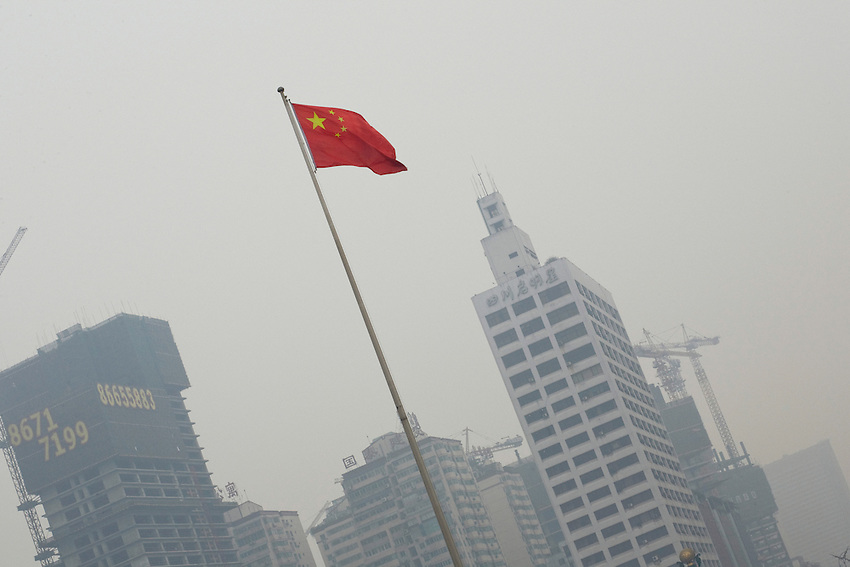 The chinese flag on the People's place of Chengdu. In the background a new modern quarter being build.