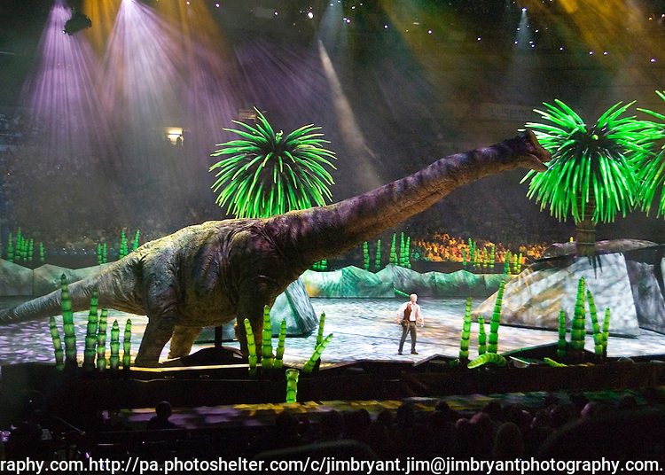 A 43 foot-tall, 75 foot-long Brachiosaurus towers over Jonathan Bliss, who portrays Huxley, the paleontologist, at the Tacoma Dome in Tacoma, Washington on July, 11, 2007. The massive creatures, which roamed the earth about 208 million years ago, have been brought back to life via truck batteries, hydraulics and puppeteers in the 90-minute show, Walking with Dinosaurs - The Live Experience, based on the award-winning BBC Television series kicked off it's seven city Summer tour in the U.S. and Canada.(© 2007 Jim Bryant Photography)..