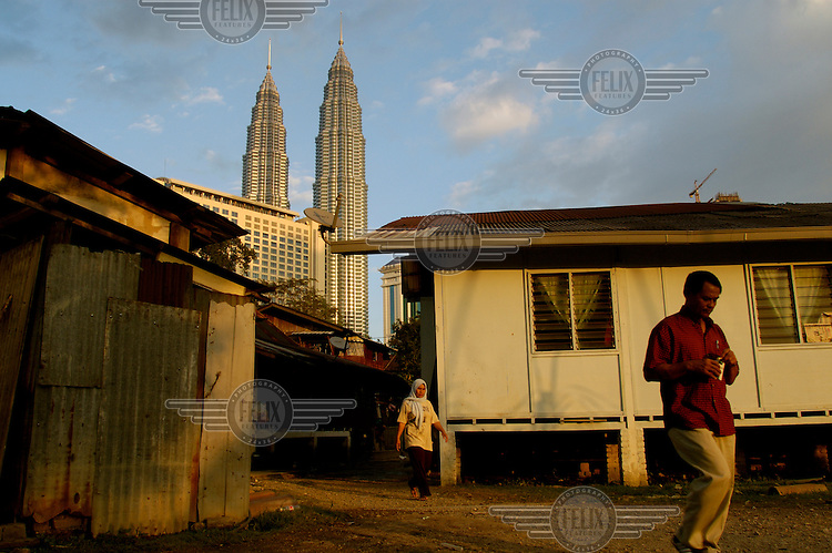 Contrast between the Petronas Twin Towers (and a luxury hotel) with a nearby slum housing area.