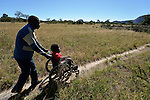 Peter Makura navigates along a path near his home in the village of Berejena, near Masvingo, Zimbabwe, with help from Anthony Dickinya, a district disability coordinator for the Jairos Jiri Association, which provided Makura with his wheelchair with support from CBM-US.