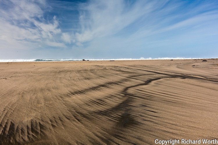 The rolling surf of the Pacific draws the horizon line  between sky and sand at Pomponio  State Beach.