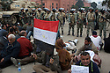 Egyptian protesters hold a position near Egyptian army soldiers during ongoing protests February 05, 2011 in Tahrir Square in downtown Cairo, Egypt. Overnight the army appeared to tighten its control of the no man's land around the square and made efforts today to convince protesters to leave voluntarily. . .Credit: Scott Nelson
