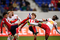 Carlos Alvarez (20) and Agustin Pelletieri (8) of Chivas USA and Peguy Luyindula (8) of the New York Red Bulls attempt to play the ball. The New York Red Bulls and Chivas USA played to a 1-1 tie during a Major League Soccer (MLS) match at Red Bull Arena in Harrison, NJ, on March 30, 2014.