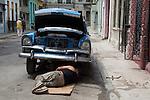 HAVANA, CUBA -- MARCH 24, 2015:   A mechanic works underneath a classic car in Havana, Cuba on March 24, 2015. Photograph by Michael Nagle