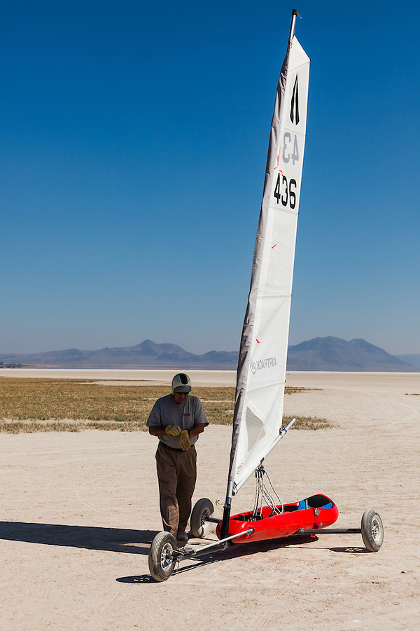 A mature male puts on a pair of gloves, preparing to take his land sailer across the Alvord Desert on a windy day in Southeast Oregon.