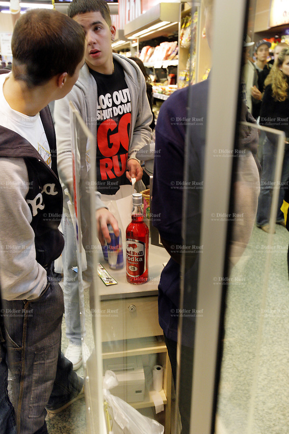 """Switzerland. Canton Bern. Bern. Aperto shop at the railway station late in the evening (23h). Two young men buy a bottle of Red Bull Vodka and two aluminium cans of Red Bull. The t-shirt of the boy says."""" Log out, shut down, go, run"""".  © 2006 Didier Ruef"""