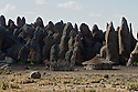 A native settlement nestled into the protective lee of the lava flow at Rafu on the edge of the Sanetti Plateau in the Bale Mountains National Park, Ethiopia, Africa.