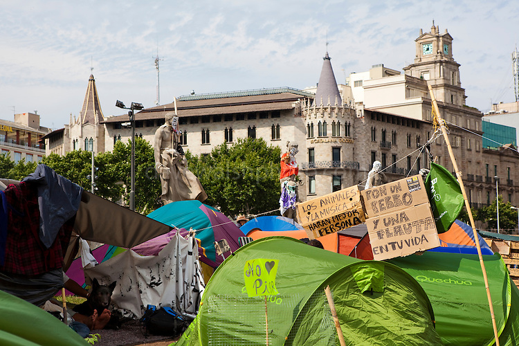 "Protest camp at Placa de Catalunya, Barcelona, Spain. The signs read: ""Animals and music will make you a better person; put a dog and a flute in your life"". The square has been relatively quiet since police attacked and beat protestors on May 27 2011."
