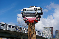 The SkyTrain passes a new public art installation entitled Trans Am Totem in Vancouver, British Columbia. This playful sculpture created by Vancouver artist Marcus Bowcott consists of five recycled cars placed on top of the trunk of an old-growth cedar tree.