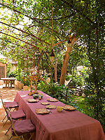 An outdoor dining area beneath a vine-draped pergola is the preferred location for lunch
