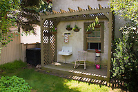 "Adorable ""room"" porch outdoors with bathroom sink, rocking chair, hanging plants, trellis, container pots, house and window framed to create a cute scene in the backyard to sit. Creating a faux washroom porch"