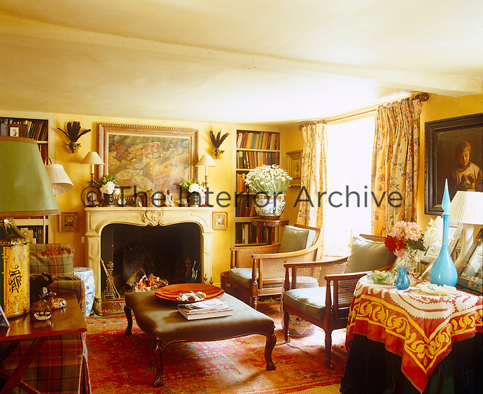 The living room is crammed with interesting antique furniture, paintings and objects
