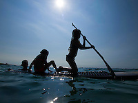A mother teaches her two young girls how to standup paddleboard at Mahai'ula Beach, Big Island.
