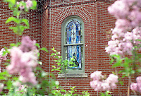 Exterior view of stained glass window on brick church with blooming azaleas
