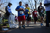 A volunteer holds a plastic bag for garbage as the trash cans were removed due to security reasons before the City Parks Foundation Run for the Parks in central Park New York, April 21, 2013. by Kena Betancur / VIEWpress