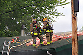 two firemen on roof of building, fighting a fire