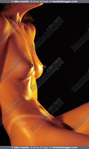 Beautiful naked suntanned shiny woman's body on black background
