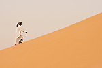 An Omani man walks up the sand dunes of the Empty Quarter, Ar Rub Al Khali, Oman.
