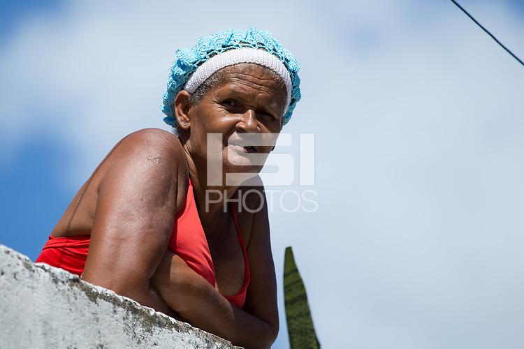 A local peers off her balcony near Arena Fonte Nova