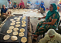 Large flat iron plates are heated by gas fire to cook the chapatis. Breads are cooked both sides for few minutes.<br /> 100 gas cilinders a day are needed in the entire Langar.