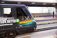 An automated rail car with a vivid photographic advertisement on its exterior departs a downtown Miami Metromover station.