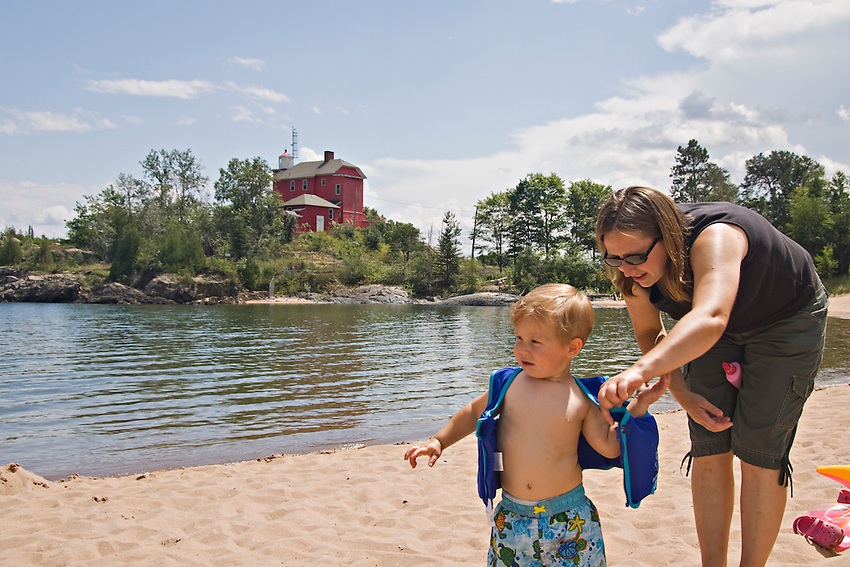 A family at McCarty Cove beach near the Marquette Lighthouse on Lake Superior in Marquette Michigan.