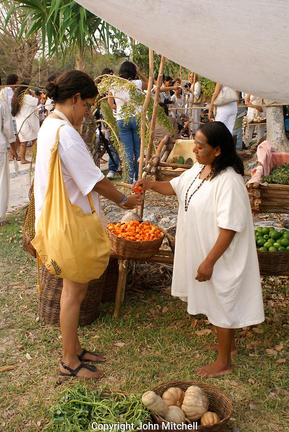 Tourist buying fruit at the recreation of an ancient Mayan market, Sacred Mayan Journey 2011 event, Riviera Maya, Quintana Roo, Mexico