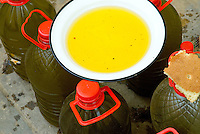 A sample bowl of yellow olive oil and bread to taste are placed on top of bottles of oil on the street in Fez, Morocco