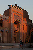 Low angle view of Museum of Applied Arts, Khiva, Uzbekistan, pictured on July 6, 2010, at sunset with a boy and his bicycle in front. The Museum of Applied Art and Life of Khorezm is a Madrasah, Kazi and Kalyan housing mainly 18th-19th century and some 20th century works by folk artists including jewellery, carpet weaving, pottery, wood and stone carving and copper coinage. Khiva, ancient and remote, is the most intact Silk Road city. Ichan Kala, its old town, was the first site in Uzbekistan to become a World Heritage Site(1991). Picture by Manuel Cohen.