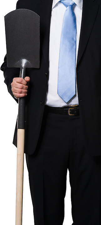 Executive showing a spade as a metaphor for digging, hard work and earth moving
