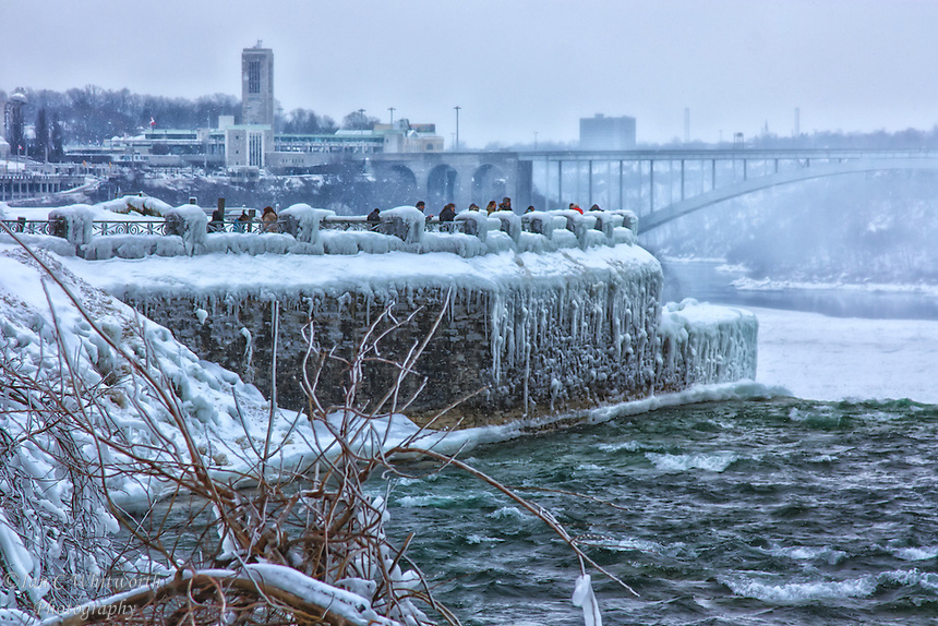 Tourists brave the Canadian winter to view Niagara Falls surrounded by ice and snow.