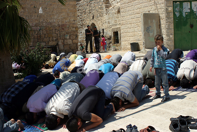 Israeli border guards keep watch as Palestinians attend the third friday prayer of Islam's holy fasting month of Ramadan outside the Ibrahimi mosque, or the Tomb of the Patriarchs, in the divided West Bank city of Hebron on August 19, 2011. Photo by Najeh Hashlamoun