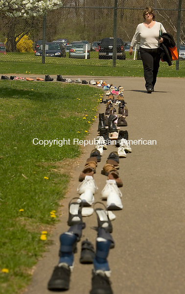 CHESHIRE, CT- 23 APRIL 2008 --042308JS03-Susan Graham, a police officer for the town of Thomaston, walks past the 250 pairs of shoes lined up as part of the Shoe Memorial Porject at the 12th annual Melanie Ilene Reiger Memorial Conference Against Violence. Wednesday at the Maloney Center for Training and Staff Development in Cheshire. The shoes represents the 250 murder victime in the State of Connecticut from 2006-2007.   The two-day conference continues today (Thursday) and is sponsored by the Melanie Ilene Reiger Memorial Foundation, the Connecticut Department of Correction and the Office for Victims of Crime. <br /> Jim Shannon / Republican-American