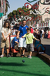 Two Italian American boys play bocce with their father at the Feast of San Gennaro - Los Angeles, CA