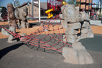 A detail view of one portion of climbing ropes at Stanton Central Park.  The ropes are suspended over either rubberized mats or wood chips.  The iconic train play structure can be seen in the background.