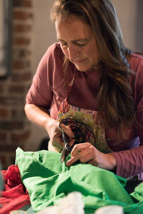 Artist in Residence, Patty Mitchell, cuts cloth at Honey for the Heart located at 29 E. Carpenter St. in Athens, Ohio.