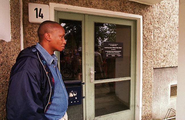 Demonstration von ca. 100 Fluechtlingen aus dem Land Brandenburg und 150 Deutschen im brandenburgischen Guben gegen die sog. Residenzpflicht (der Ort in dem das jeweilige Fluechtlingsheim ist, darf nicht verlassen werden) und gegen die Verschleppung des Prozesses gegen rechtsradikale Jugendliche aus Guben, die den algerischen Fluechtling Farid Guendoul Omar Ben Noui in der Nacht zum 13. Februar 1999 zu Tode hetzten.<br /> Hier: Ein Demonstrationsteilnehmer gedenkt Farid Guendoul Omar Ben Noui vor dem Haus in dem er verblutete.<br /> 8.7.2000, Guben<br /> Copyright: Christian-Ditsch.de<br /> [Inhaltsveraendernde Manipulation des Fotos nur nach ausdruecklicher Genehmigung des Fotografen. Vereinbarungen ueber Abtretung von Persoenlichkeitsrechten/Model Release der abgebildeten Person/Personen liegen nicht vor. NO MODEL RELEASE! Nur fuer Redaktionelle Zwecke. Don't publish without copyright Christian-Ditsch.de, Veroeffentlichung nur mit Fotografennennung, sowie gegen Honorar, MwSt. und Beleg. Konto: I N G - D i B a, IBAN DE58500105175400192269, BIC INGDDEFFXXX, Kontakt: post@christian-ditsch.de<br /> Bei der Bearbeitung der Dateiinformationen darf die Urheberkennzeichnung in den EXIF- und  IPTC-Daten nicht entfernt werden, diese sind in digitalen Medien nach &sect;95c UrhG rechtlich gesch&uuml;tzt. Der Urhebervermerk wird gemaess &sect;13 UrhG verlangt.]