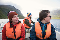 Female hikers on STF water taxi across lake Teusjaure, Kungsleden trail, Lapland, Sweden